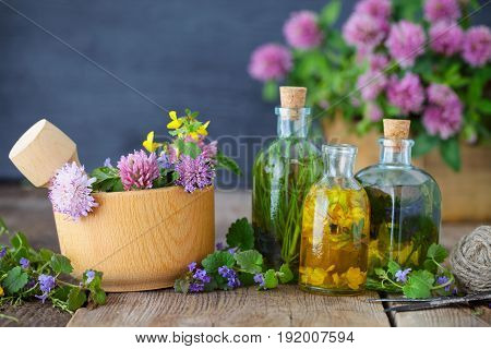 Bottles of tincture or infusion of healthy herbs healing herbs and wooden mortar of flowers on rustic table. Herbal medicine.