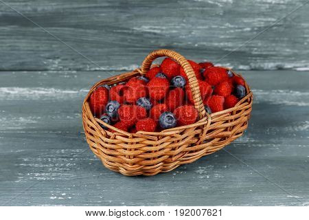 Basket With Berries On Old Boards