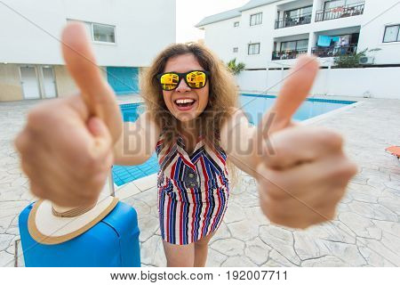 Girl on summer holidays on the background of pool, dressed striped dress and sunglasses.