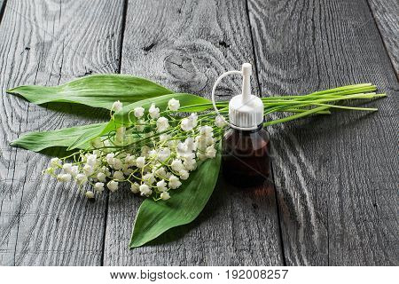 Lilies of the valley (convallaria majalis) and essential oil in vial on dark wooden table. Aroma of the lily-of-the-valley is actively used in cosmetics production of perfumes hygiene products
