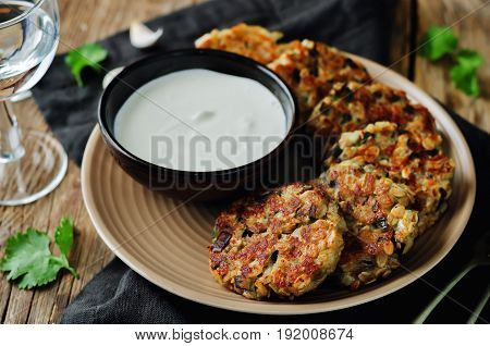 Eggplant cheese cilantro oats fritters on a wood background
