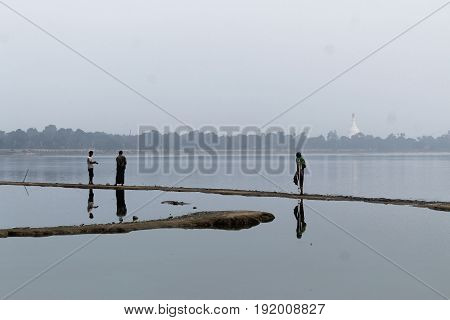 U-BEIN BRIDGE/AMARAPURA, MYANMAR JAN 22: Fishermen are walking on sandbanks on the  Taungthaman Lake to watch their nets January 22, 2016, U-Bein bridge/Amarapura