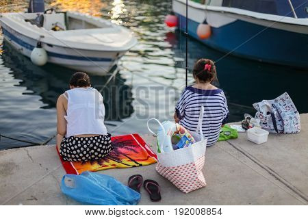 Bali Island Crete Greece - June 30 2016: Two greek women are catching fish from the pier located on Crete island in Greece.