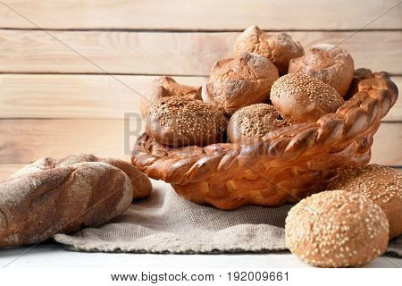 Baked basket with rye buns on wooden background