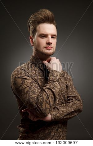 MAN haircut. Stylish young man with trendy hairstyle pose in studio. In shirt with pattern. Vogue.