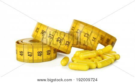 Weight loss supplements and measuring tape isolated on white