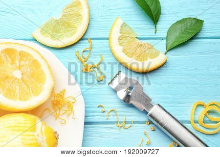 Composition with cut lemon, zest and special tool on wooden table, closeup