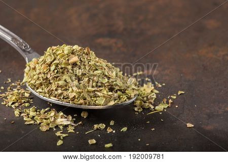 Spoon filled with dried oregano on rusty background