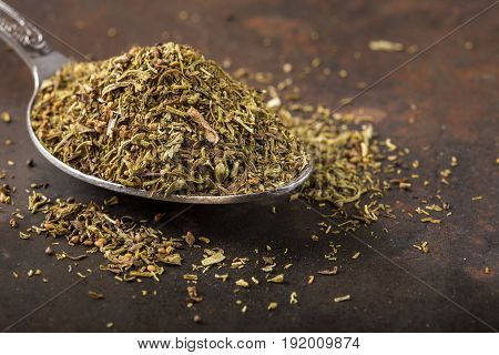 Spoon filled with dried thyme on rusty background