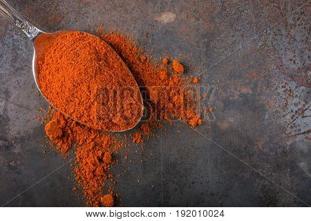 Spoon filled with paprika powder on rusty background with copy space