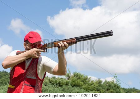 Man shooting skeet with a shotgun. Shotgun.