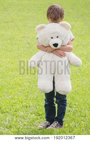 Sad boy embracing hid teddy bear. Outdoor, summer day.