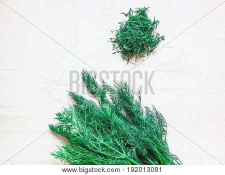Bunch of dill on a wooden board. Next to a handful of chopped dill.