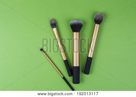 Make up brushes on greenery background. Top view.