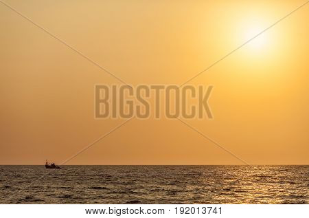 Small fishing ship on ocean open spaces under beams of the sun. The picture for a background or a screensaver in amber-yellow tones.