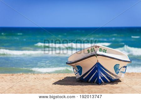 The bright boat of white color with blue inserts number on the board and with the image of eyes on a nose is on the sandy coast against the background of clear sky and blue waves of the southern sea as reminiscence of hot and bright summer holiday.
