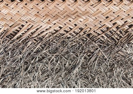 The lodge roof covering in tropics consisting of the dry bound palm leaves. Natural material for the background connected with ecology and natural organic materials.