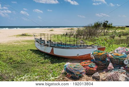 The big fishing boat on the grass of sandy ocean coast with full baskets with color fishing nets and buoyes for them.