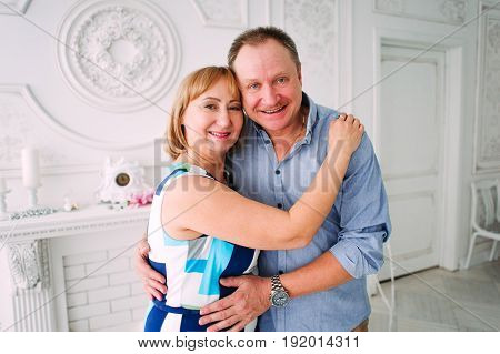 Happy And Smiling Senior Couple In Front Of White Wall