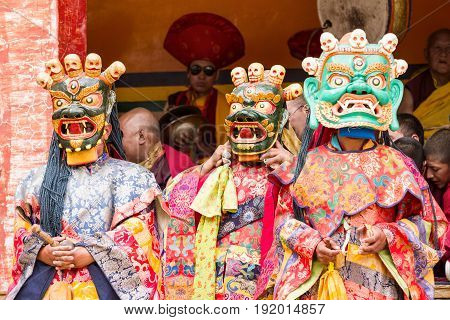 Lamayuru India - June 17 2012: monks perform a religious masked and costumed mystery dance of Tibetan Buddhism and another monks at the back play ritual music during the Cham Dance Festival in the Lamayuru monastery India.