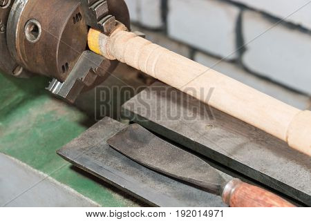 Old lathe for processing wood with a wooden bar in a collet