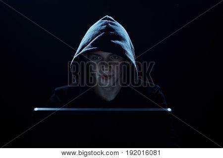 A hacker in a hood, a hacker breaks into networks, a hacker on a dark background.