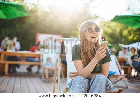 Girl eating ice cream laughing. Portrait of young female sitting in a park on a sunny day eating icecream looking off camera wearing glasses enjoying summer.
