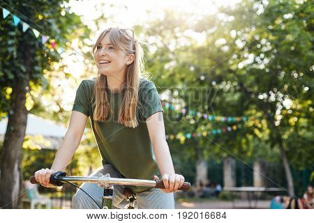 Blonde woman riding a bike. Portrait of young nordic girl riding a bycicle in a city park smiling off camera looking for her boyfriend on a sunny summer day.
