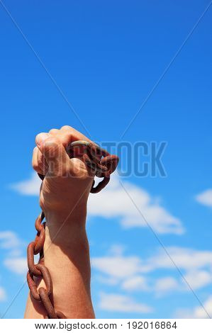 male hand holds a rusty metal chain with large links against the blue sky