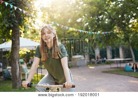Blonde woman riding a bike. Portrait of young nordic girl riding a bycicle in a city park smiling on camera looking happy on a sunny summer day. Healthy lifestyle concept.