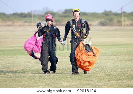 RUSTENBURG SOUTH AFRICA - April 28 2017: National Skydiving Championships. Love is in the air! Man and woman skydivers walking hand in hand after successful landings