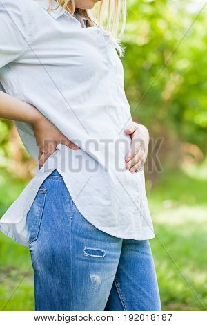 Close up picture of a pregnant woman holding her belly in the first trimester outdoor
