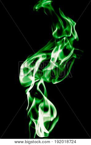 Green flame of fire on a black background .