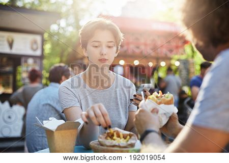 Couple eating fries and burger on a sunny summer day in park. Junk food concept.