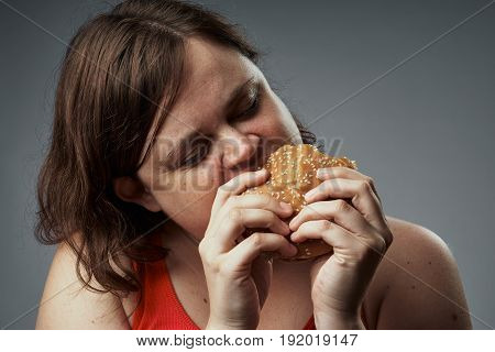 Hungry woman, a woman with a hamburger eating a hamburger, harmful food, a woman on a gray background portrait.