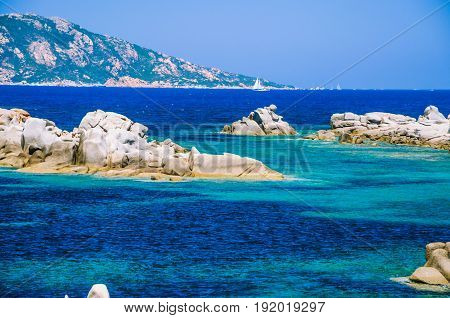 Granite rocks in sea, amazing azure water, white sailboat in background near Porto Pollo, Sardinia, Italy.