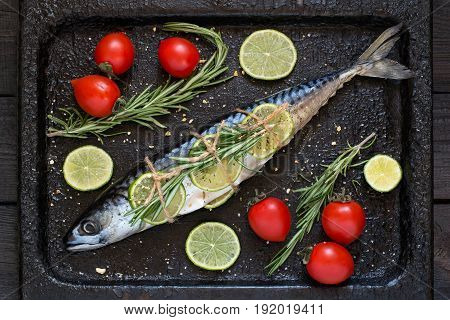 Mackerel or scomber with lime rosemary cherry tomatoes and spices. Preparing mackerel for baking on an old scratched iron pan