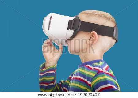 A Surreal photo of a young boy with VR Goggles with an isolated on blue background with clipping mask