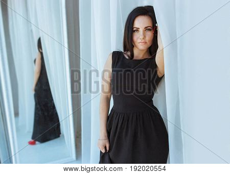 Portrait of attractive exotic latina woman with long dark hair wearing black dress. Girl standing at the window next to the mirror