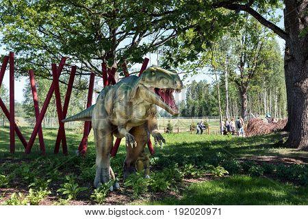 LEDMANE, LATVIA - JUNE 2017: Dinosaur sculpture in forest of AB Park nature park