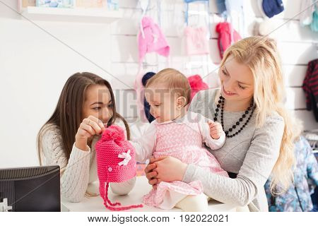 The seller shows girl winter pink hat with pompom to select purchases