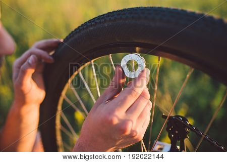 The Guy Fixing The Bicycle Wheel In The Field At Sunset