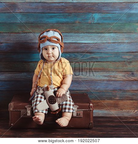 Boy in a knitted pilots cap plays with toy airplane, sitting on an old-fashioned suitcase