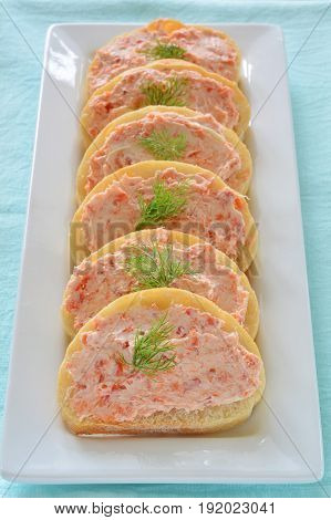 Smoked salmon and cream cheese on cibatta rounds appetizers in vertical format. Shot in natural light.