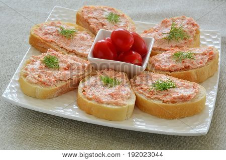 Smoked salmon and cream cheese on cibatta rounds appetizers in horizontal format. Shot in natural light.