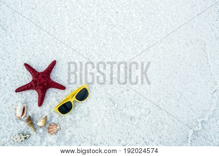 Sunglasses, shell and starfish on a white background. Vertical