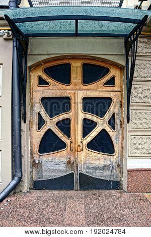 An old brown wooden door with a visor on the facade of a private building