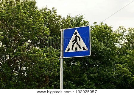 Road sign pedestrian crossing on a background of greenery