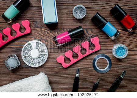 manicurist work place with manicure set and nail polish for hands care on wooden background top view
