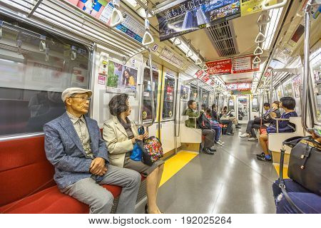 Tokyo, Japan - April 17, 2017: asian people subway wagon inside in Toei Oedo Line, a subway line in Tokyo. On maps and signboards, the line is shown in magenta and the stations carry the letter E.